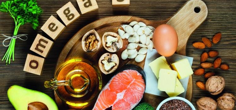 Omega-3-haltige Nahrungsmittel auf Tisch verteilt. Omega 3 steht auf Holzwürfeln. Omega 3 Fettsäuren