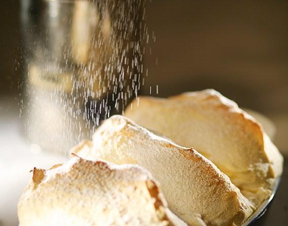 Salzburger Nockerl werden mit Staubzucker bestreut. Rezepte aus Salzburg