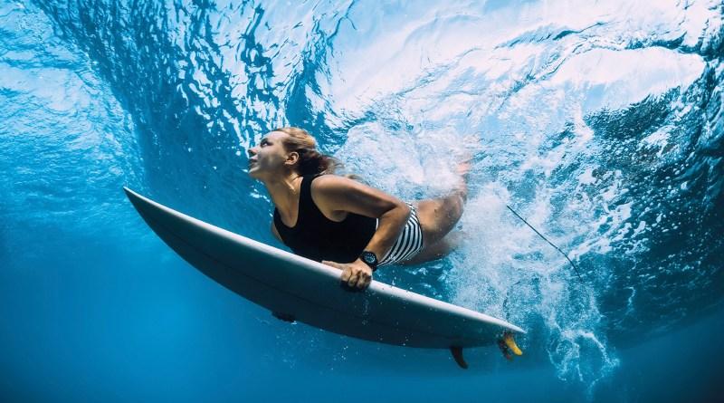 Frau taucht mit Surfboard unter Wasser ein. Taucherohr