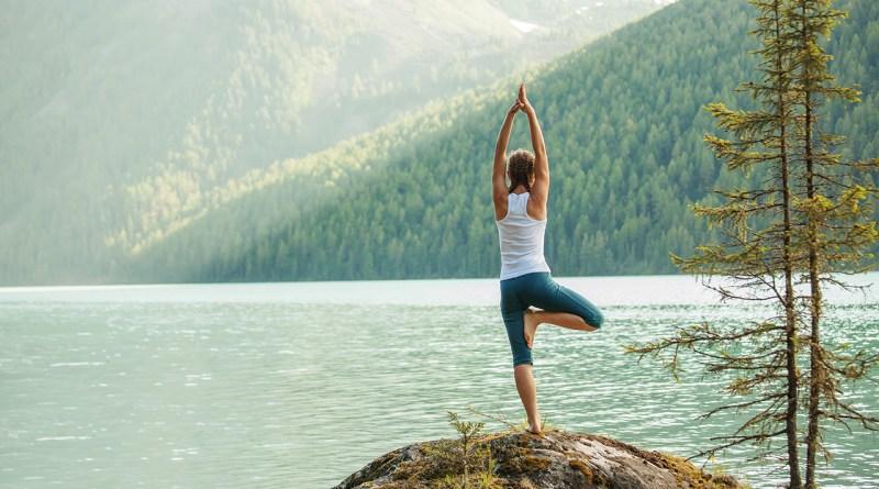 Frau macht Yoga in Natur. Am See und in den Bergen. Säure-Basen-Haushalt