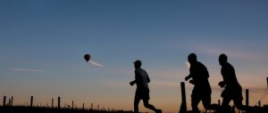 A group of runners at dusk with a balloon in the background