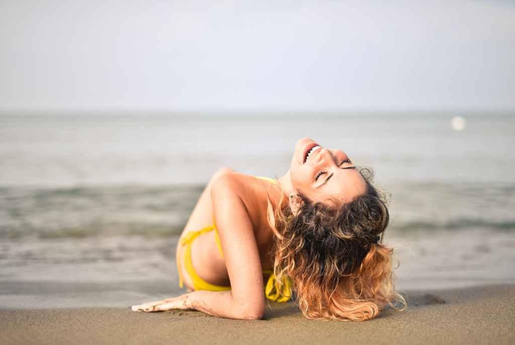 woman in yellow bikini lying on seashore