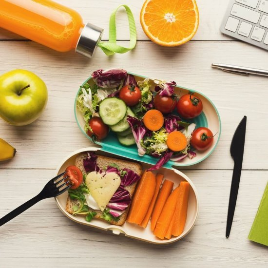 Healthy snack at office workplace. Eating organic vegan meals from take away lunch box at wooden working table with computer keyboard, top view