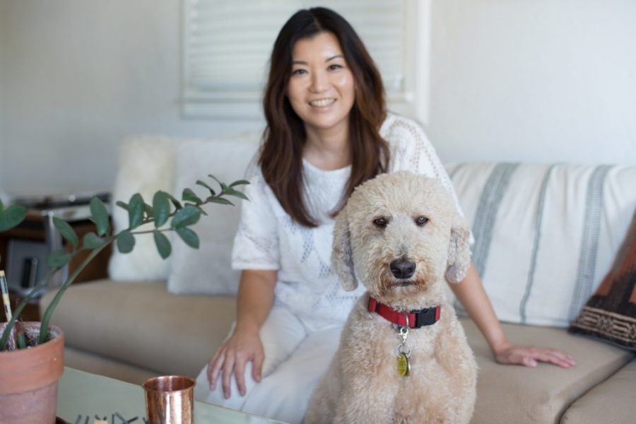 Dr. Patti Kim sitting on cream couch. Labradoodle with red collar in foreground