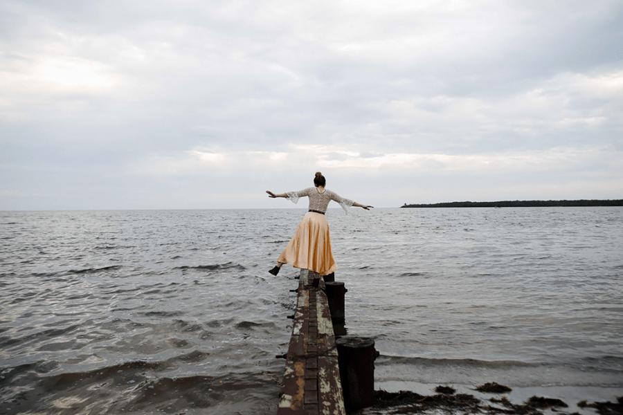 Woman balancing on dock over ocean