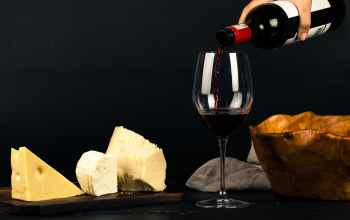 photo of person pouring wine into glass besides some cheese pairings