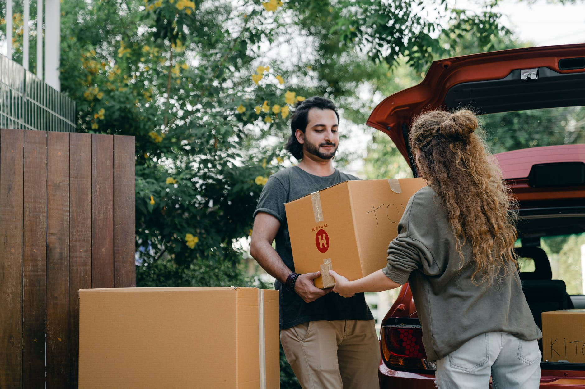 couple passing carton box to each other while unpacking car