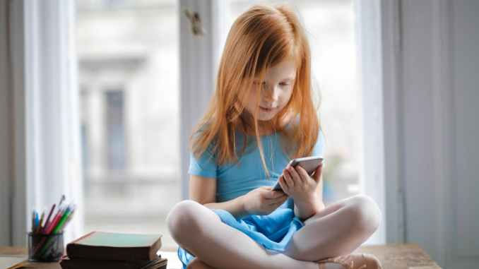 calm small ginger girl sitting on table and using smartphone in light living room