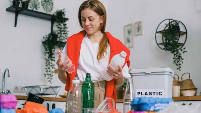 positive female sorting plastic bottles in kitchen in apartment