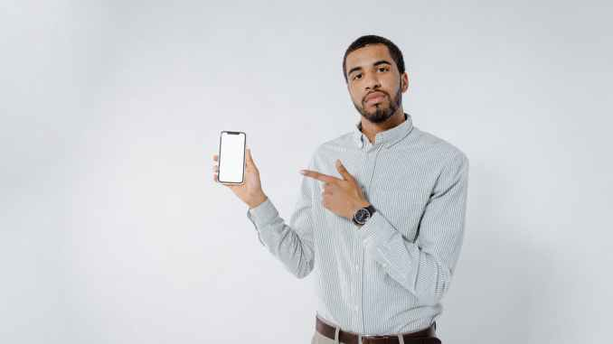 man in long sleeve polo holding a mobile phone