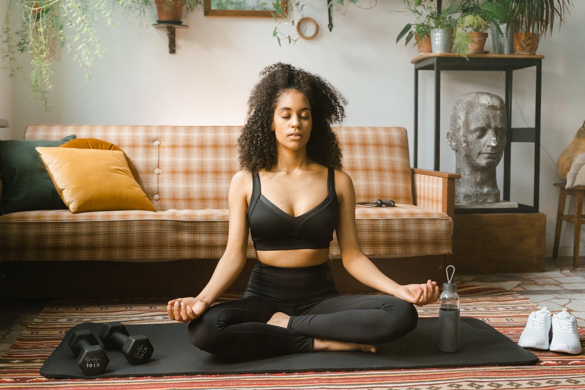 woman in black activewear meditating indoors