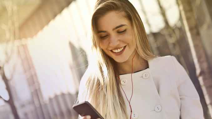 selective focus photography of woman wearing chef uniform and holding smartphone while smiling