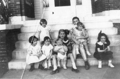 Front row: Ann Jordan age 6, Ann Applegate age 2 1/2, Jo Ann Keller age 8 or 9 holding some boy, Margaret Robb Jones age 6 Back row: Sarah Jane Jordan age 4, Katherine Buchanan age 13 holding Betty Buchanan, age 2.