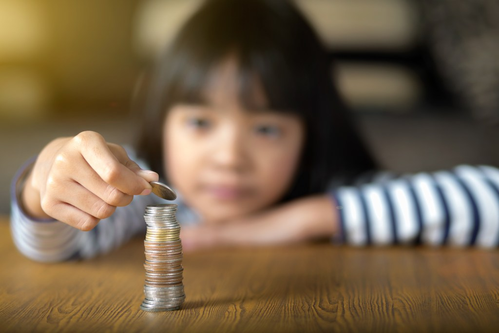 Little girl counts his coins on a table, Select focus at coins