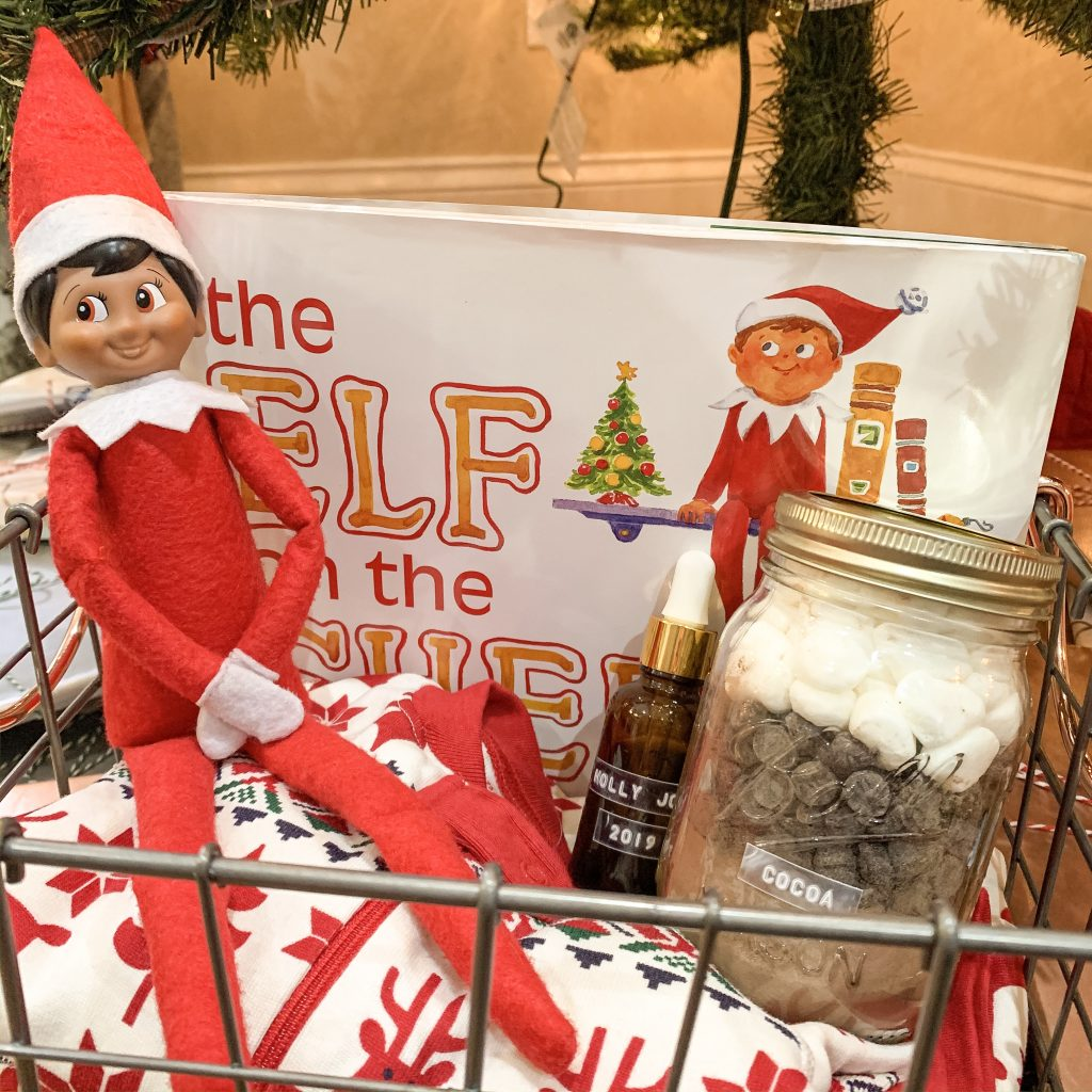 A basket sitting under a Christmas tree full of holiday essentials like an Elf on the Shelf, a mason jar filled with hot chocolate, a Holly Jolly 2019 Essential Oil Blend, and Christmas pajamas from Hanna Andersson.