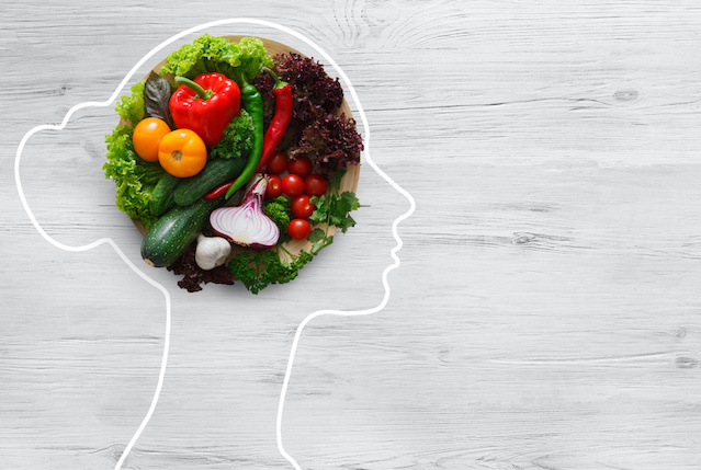 Health in your brain. Fresh vegetables in woman head symbolizing health nutrition on gray background