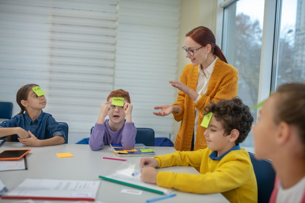 Use these fun tips for teaching vocabulary to students and children. Learning while playing. Cheerful young woman clapping her hands standing between pupils with stickers on their foreheads