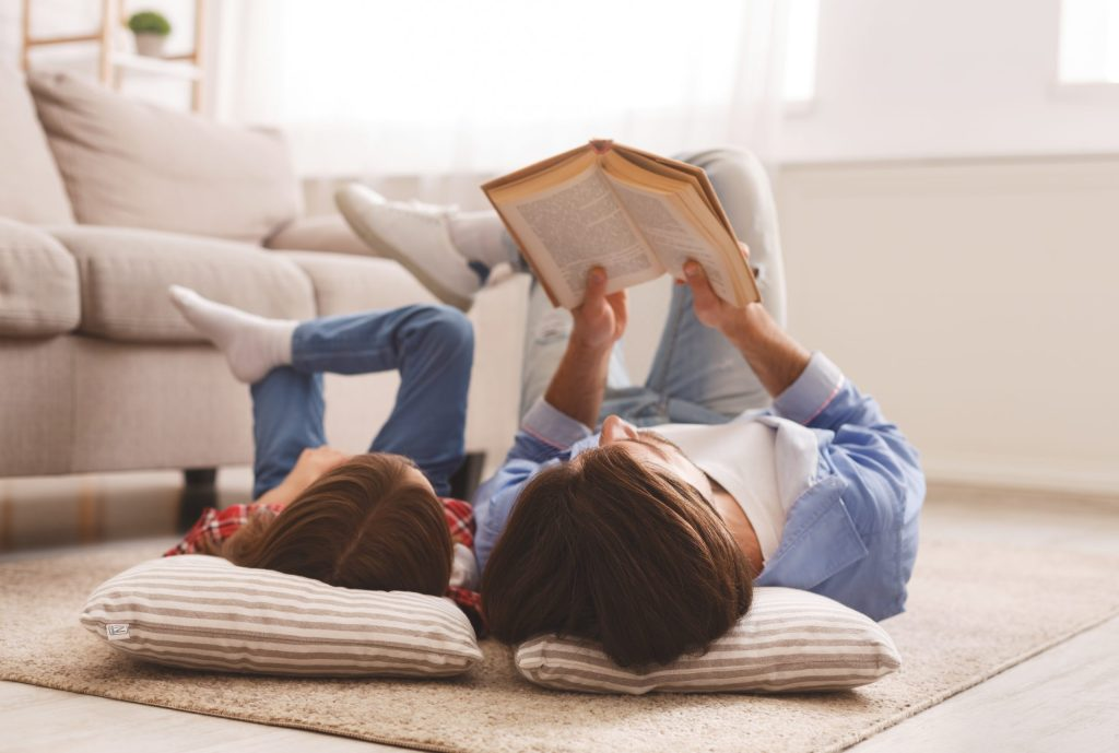 Little daughter and daddy enjoying time together, laying on floor at home, man reading book to his cute daughter, empty space