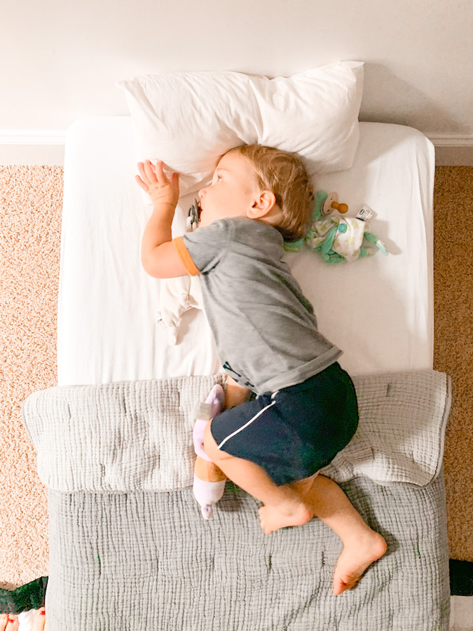 Toddler laying in a big kid bed