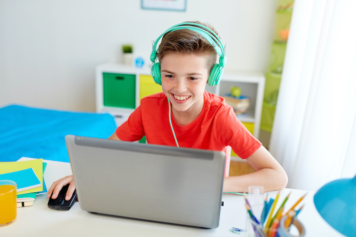 technology, gaming and people concept - boy in headphones participating in distance learning for a middle school classroom