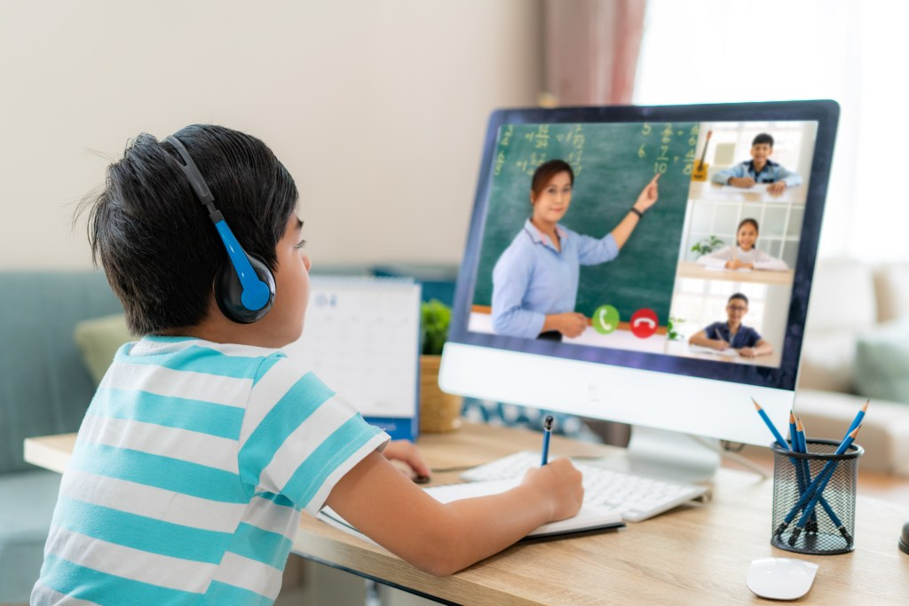 Youngg boy on a student video conference e-learning with teacher and classmates on computer in living room at home.