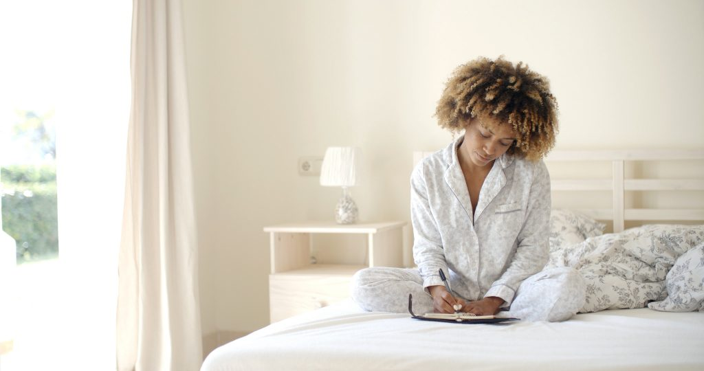 Young woman writes a diary while lying in bed in the morning