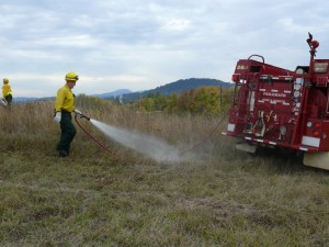 Wetting down the mowed fire line to control the perimeter of the fire.