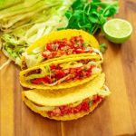 beef tacos with shredded lettuce and tomato salsa stacked together on a wooden board