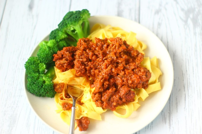 Slow Cooker Spaghetti Bolognese on a bed of pasta with some broccoli.