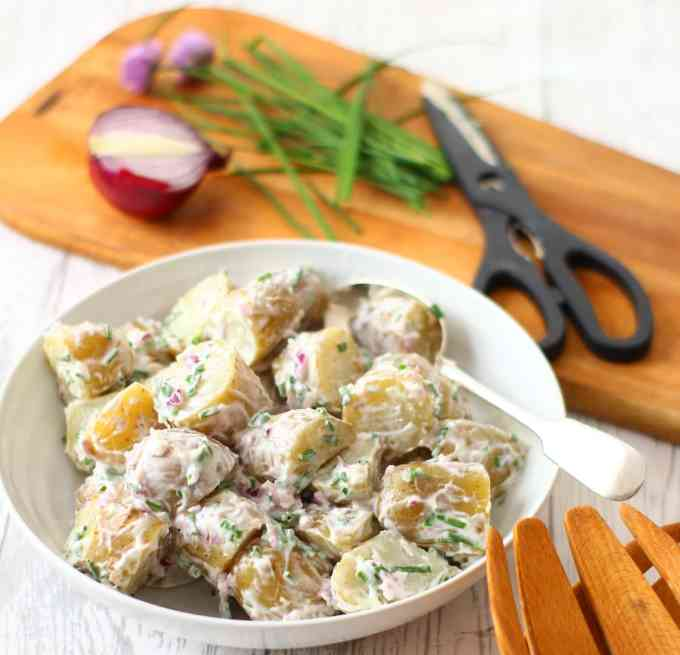Potato Salad in a bowl with chives and red onion on a wooden board
