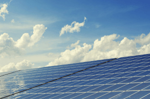 Solar panels with a mostly sunny sky