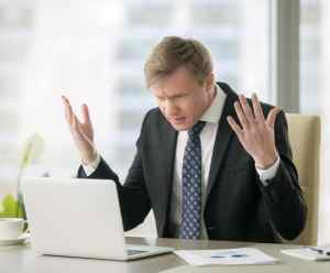 Businessman in office looking frustrated with his laptop