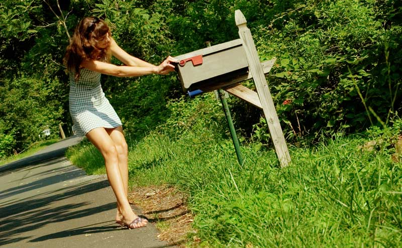 woman opening her postal mail box by the road