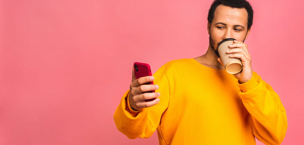 handsome man using mobile phone and drinking take away coffee cup isolated over pink scaled - Using WPTouch To Optimize Your Website