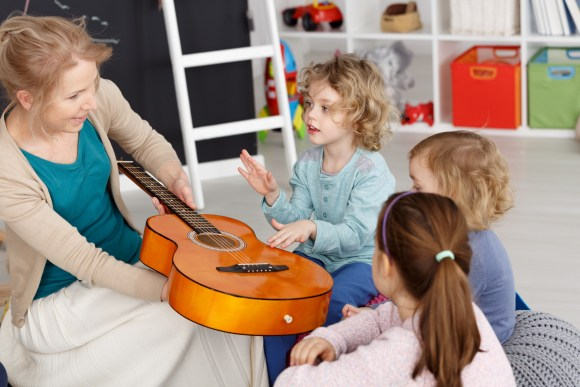 Young teacher having music lesson with small kids in kindergarten