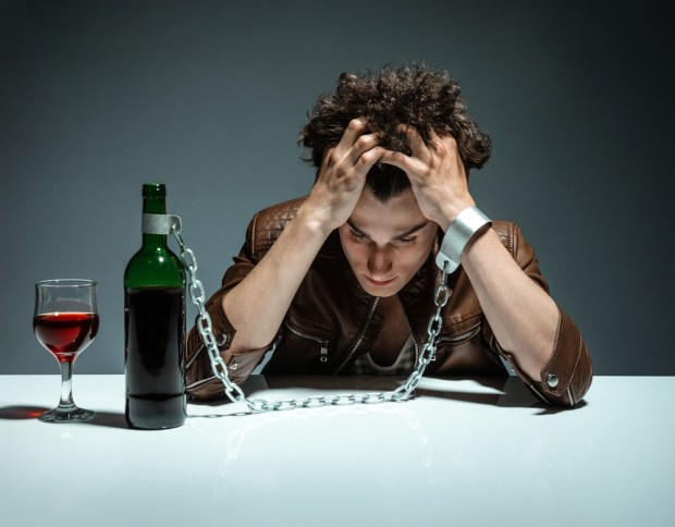 Intoxicated man sitting alone / photo of youth addicted to alcohol, alcoholism concept, social problem