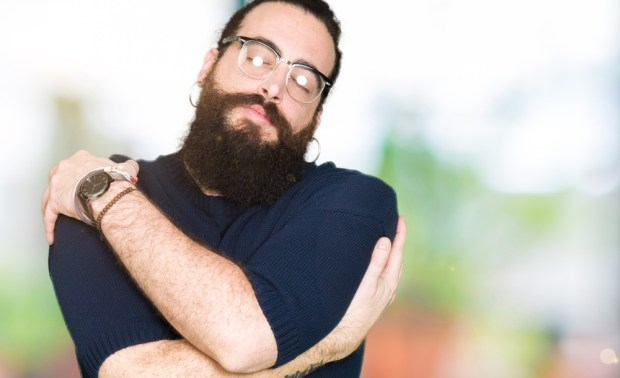 Young hipster man with long hair and beard wearing glasses Hugging oneself happy and positive, smiling confident. Self love and self care