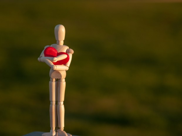 Wooden mannequin embracing his heart with his his hands Concept of romanticism and love