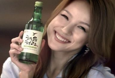 chica coreana sonriendo sosteniendo una botella de soju