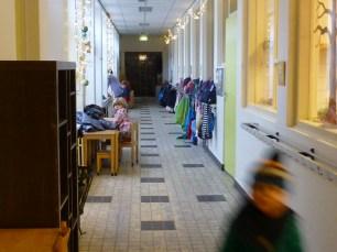 Niña trabajando en el pasillo mientras sus compañeros están en clase