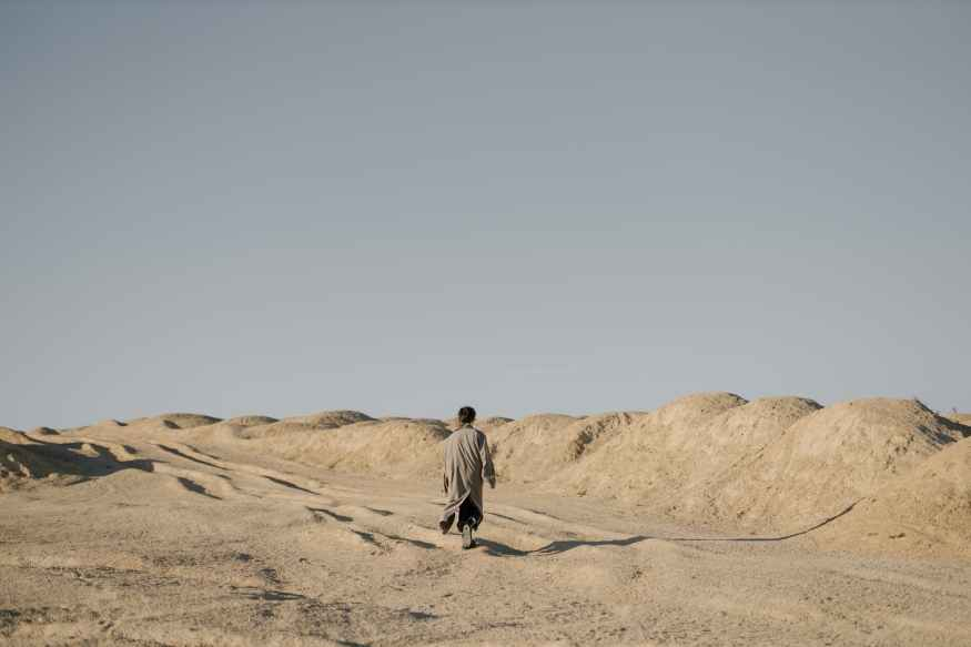 Hombre de chaqueta gris caminando sobre arena marrón