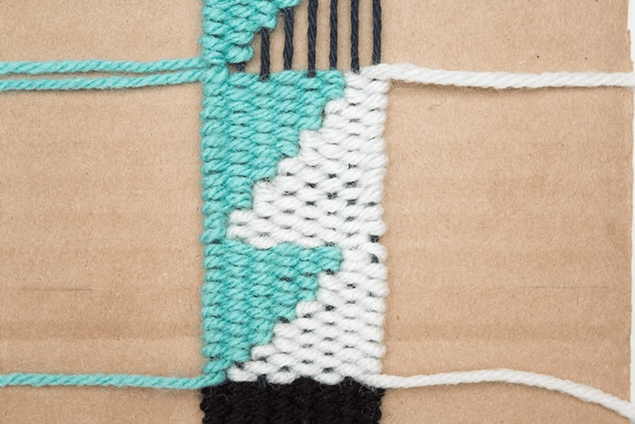 Fill the negative space by weaving with white yarn.