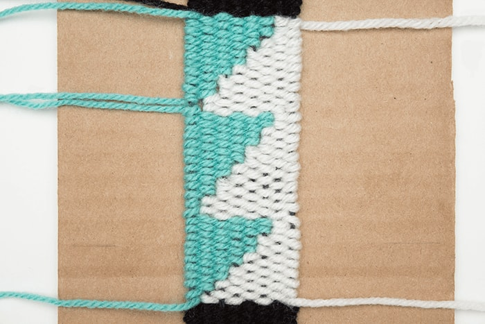 Completely fill in the negative space with white yarn for this DIY woven bookmark.