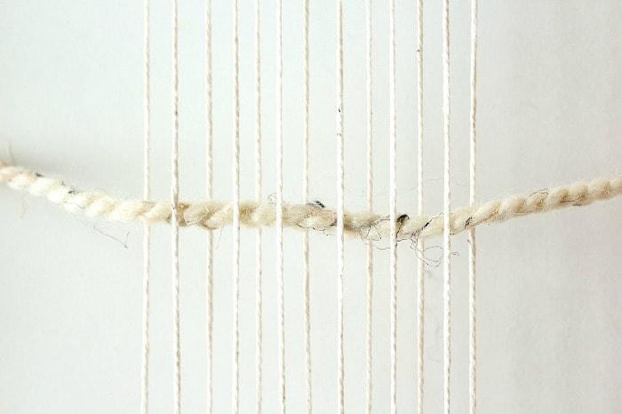 DIY mini framed weaving - feed first yarn through.