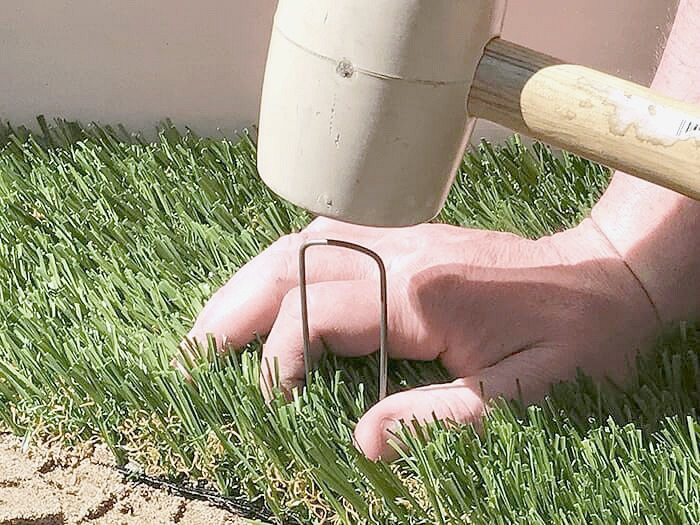 Learn how to lay artificial grass with some soil, landscape staples and a mallet.