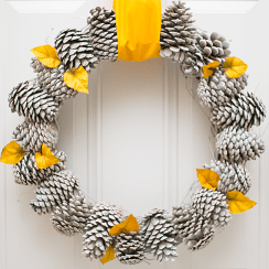 Using just a few materials, this pretty pine cone wreath is simple to create and makes a great statement on your front door. It's the perfect fall wreath that transitions beautifully into winter by swapping out the ribbon and leaf embellishments.