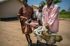 Panthou village, Aweil South county, Northern Bahr el Ghazal state, South Sudan October 14, 2015 Thirty-two year old Arek Nuoi, mother of four, is carried by her family members to a hospital bed at Panthou Primary Health Care Center, where she will receive urgent treatment for acute malaria. She arrived unconscious, transported in a chair her family had tied to the seat of a bicycle, which they pushed for one and a half hours from their home village of Maper. She had first shown signs of illness the previous night, complaining of headache and bodily pains. In the morning, she began to vomit and fainted. The health care center at Panthou is currently the only place where patients might be able to receive free treatment and medicine for malaria in the remote rural county of Aweil South. The center has only two staffs - both medical assistants - qualified to diagnose and treat patients, yet was treating approximately 150 malaria patients per day. In October 2015, the center had just received a supply of ACT oral medication for malaria, which they had been out of stock for two months. With the high number of patients, this new supply would be depleted in a week or two. The center also had a low stock of quinine, which they reserved for serious cases. There were no RDTs (rapid detection tests) in stock, so diagnosis could only be done clinically based on symptoms observed.