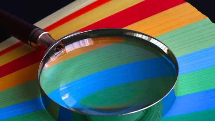 A glass metaphorically used be workplace investigators over coloured paper arranged in Pride colours.