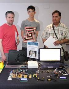 Alumno ganador con su profesor y su trabajo durante su valoración.