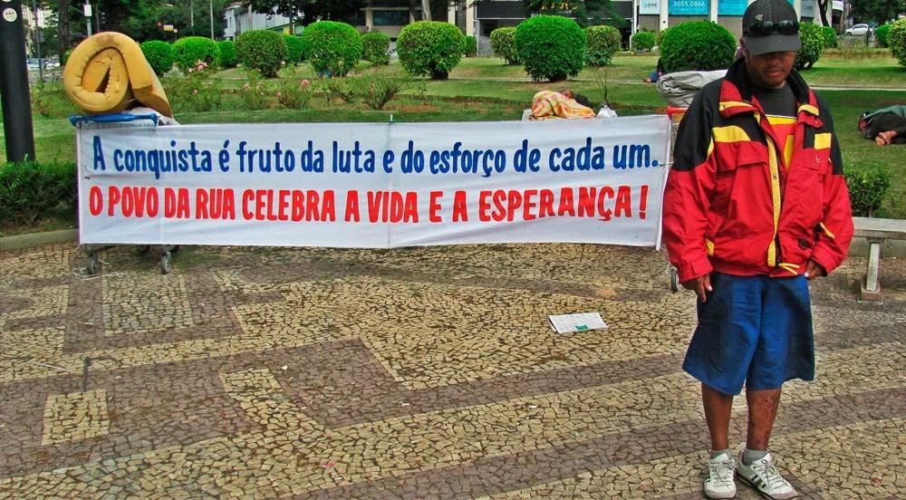Gil, morador de rua, protesta contra preconceito em praça de Belo Horizonte no dia de abertura da Copa do Mundo. Segundo ele, um policial ameaçou atear fogo aos carrinhos caso não removesse a faixa. (Imagem: Bruno Fonseca: Agência Pública)